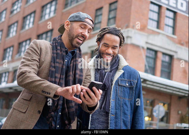 Smiley homosexual couple looking at smart phone in street - Stock Image