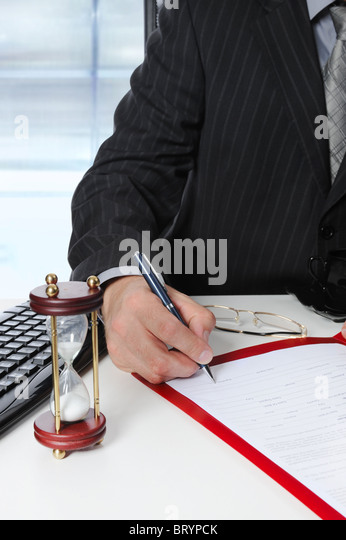 Businessman signs a document at the office - Stock Image