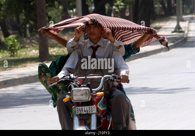 Lahore. 17th Apr, 2017. Pakistani school boys cover their heads during heat wave in eastern Pakistan's Lahore, - Stock Image