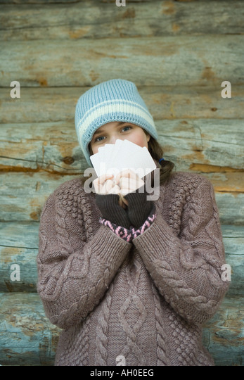 Teenage girl looking over cards, dressed in winter clothing, portrait - Stock Image