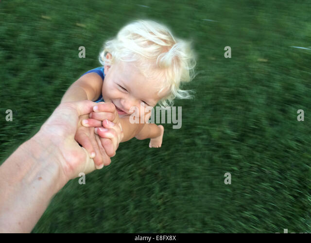 Person's hand spinning a toddler around - Stock Image