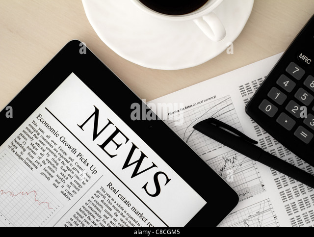 Desktop with a Tablet PC, which shows the latest news on screen. - Stock Image