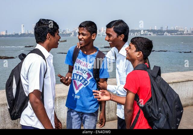 Mumbai India Asian Churchgate Marine Drive Back Bay Arabian Sea teen boy student friends talking - Stock Image