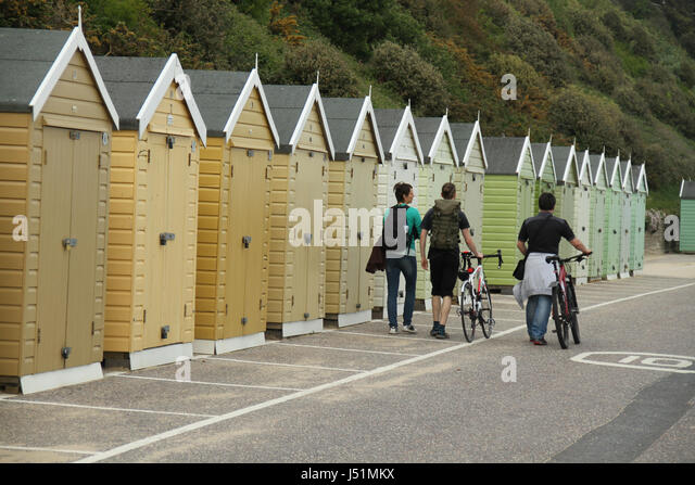 Bournemouth, UK -  11 May: People walking by an array of beach huts located on Bournemouth beach. General view of - Stock Image