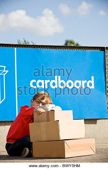 A young boy sitting with cardboard boxes in a recycling centre - Stock Image
