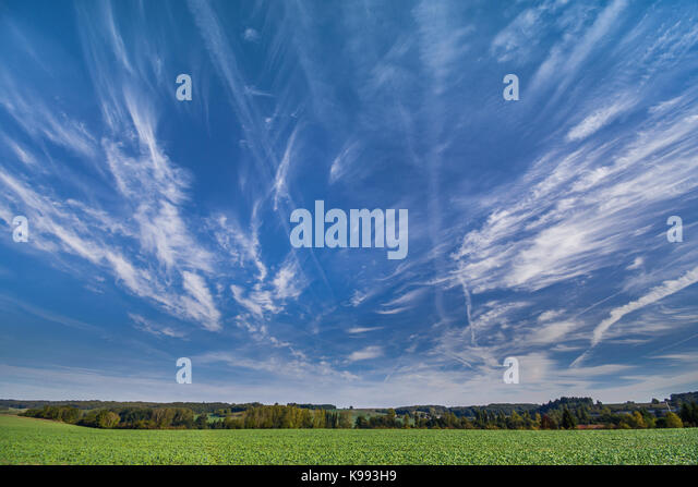 Cirrus clouds and aircraft contrails, France. - Stock Image