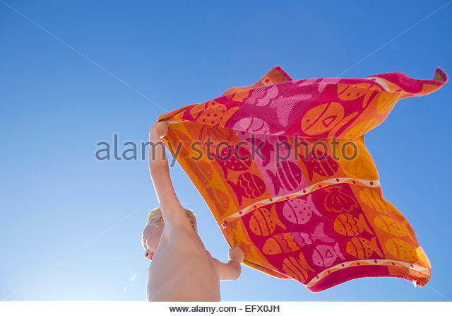 Portrait of boy holding towel above head in the wind on sunny beach - Stock-Bilder