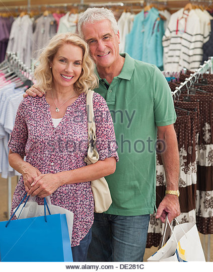 Couple carrying shopping bags in store - Stock Image