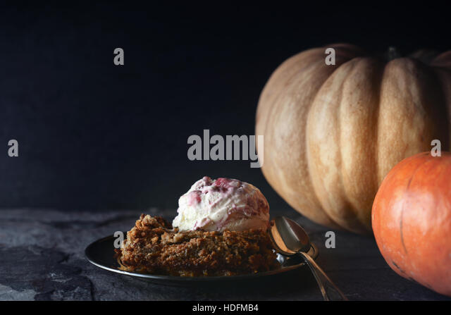 Pumpkin dump cake with ice cream on the stone table horizontal - Stock Image