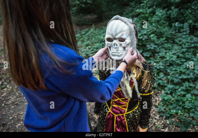 A girl helping her friend with her costume for Halloween Night. - Stock-Bilder