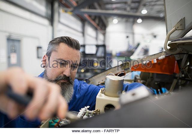 Helicopter mechanic repairing engine - Stock Image