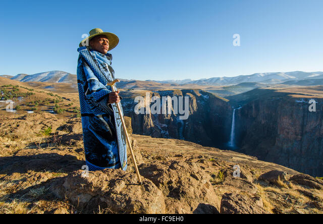 A local sheep shepherd converges on the cliffs of Maletsunyane Falls in rural Lesotho. - Stock Image