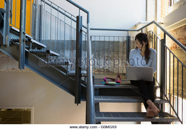 Barefoot businesswoman texting and using laptop on staircase - Stock-Bilder