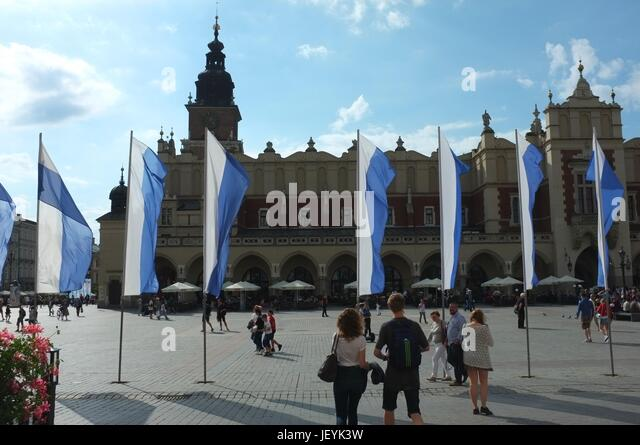 Flags in front of the Cloth Hall (Sukiennice) in Main Square (Rynek Główny) of the Old Town in Krakow, Poland, - Stock Image