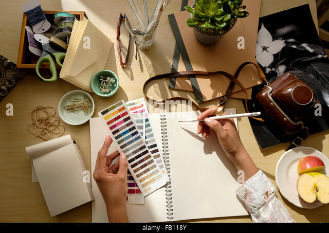 Overhead view of female hands writing in note pad - Stock Image