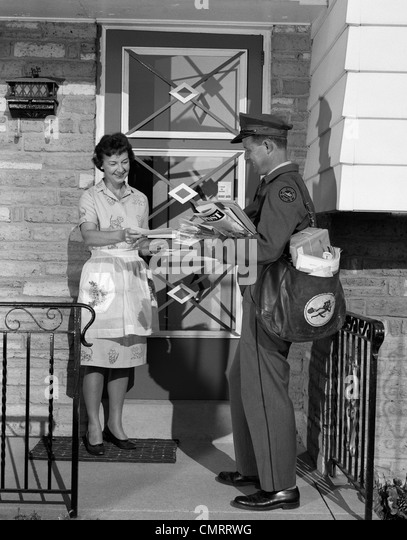 1960s MAN MAILMAN DELIVERING MAIL TO WOMAN HOUSEWIFE IN FRONT OF SUBURBAN HOUSE OUTDOOR - Stock Image