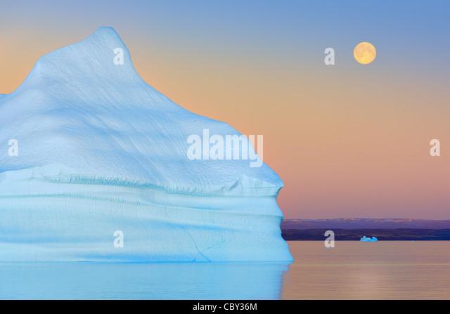 Iceberg at Sunset and Moonrise at Hall Bredning, Scoresbysund, Greenland - Stock Image