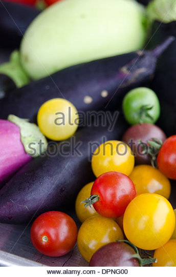 Detail of summer vegetables including eggplant and cherry tomatoes. - Stock Image