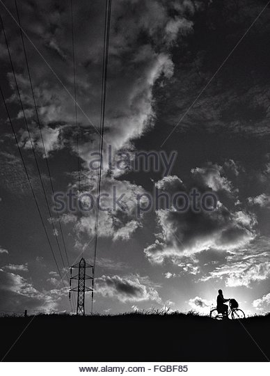 Silhouette Person Cycling On Field With Electricity Pylon Against Cloudy Sky - Stock Image