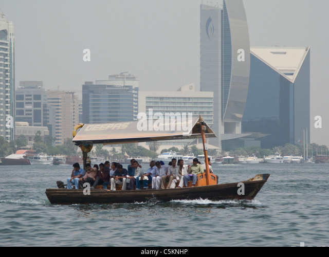 An Abra, a traditional wooden water-taxi boat, crossing The Creek in Dubai, United Arab Emirates, with modern buildings - Stock Image