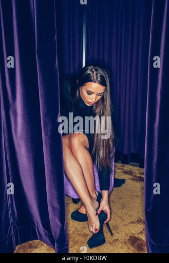 Young woman fitting high heels in a clothing shop - Stock Image
