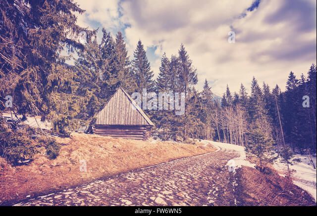 Vintage toned wooden hut by cobblestone road in Tatra Mountains, end of winter and beginning of spring when first - Stock Image
