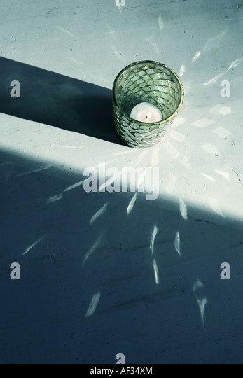 a candle in light creating a decorative pattern - Stock Image