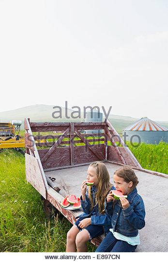 Girls eating watermelon on farm - Stock Image