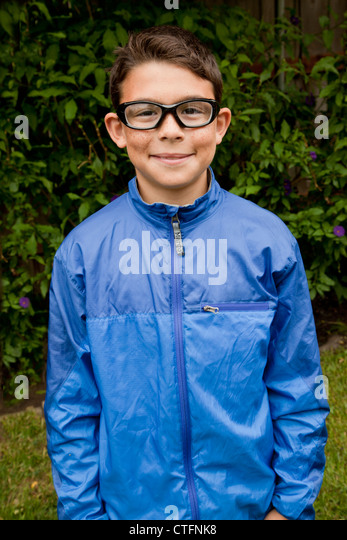 Boy in a blue windbreaker smiling at the camera. - Stock Image