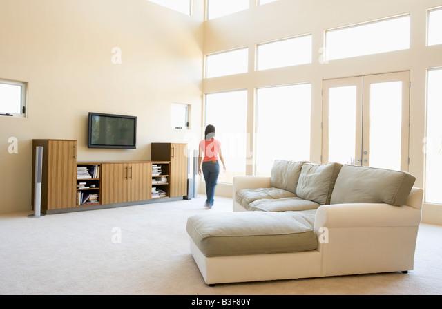 Woman walking through living room - Stock Image