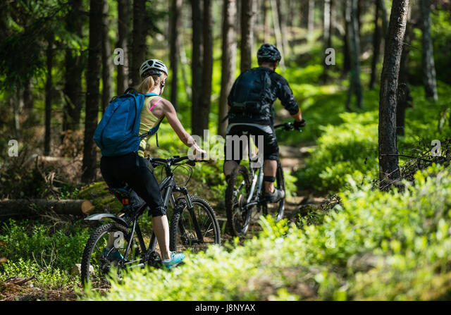 Man and woman riding bicycles in forest - Stock-Bilder