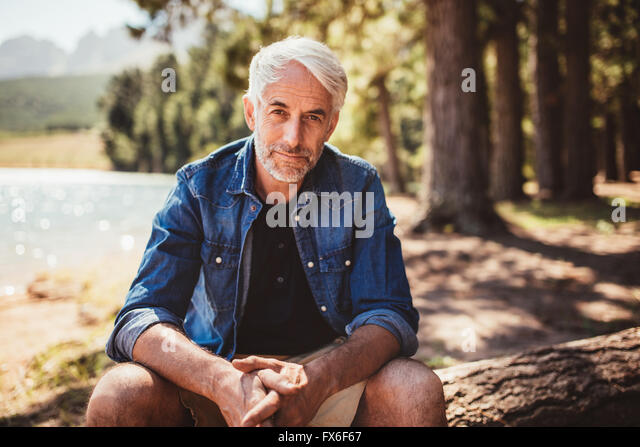 Portrait of mature man sitting near a lake staring at camera. Senior caucasian man relaxing on a log by the lake - Stock Image