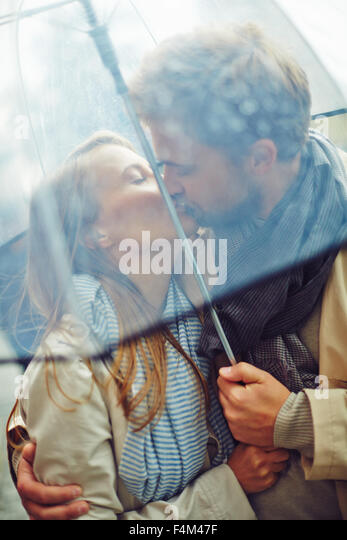 Amorous man and woman kissing under umbrella - Stock-Bilder