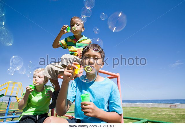 Boys blowing bubbles on monkey bars at playground - Stock Image