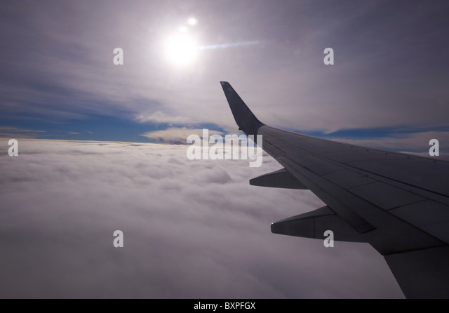 Looking out over clouds through airliner window - Stock Image