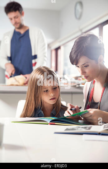 Mother and daughter reading book together - Stock Image