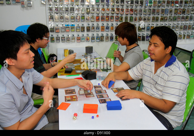 Bangkok Thailand Chatuchak Phaholyothin Road Asian man teen boy trading cards fantasy role playing GateCrash card - Stock Image