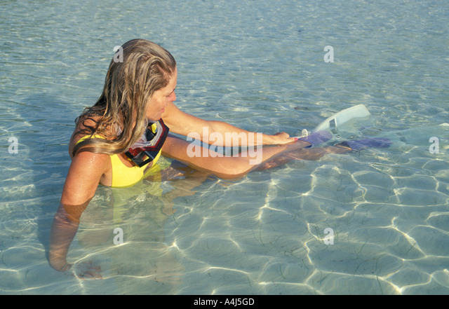 Snorkeling woman tropics putting on fins - Stock Image