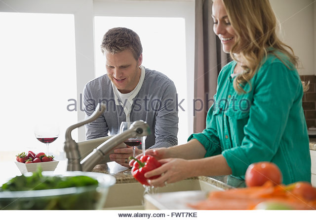 Woman washing vegetables in kitchen while husband uses digital tablet - Stock Image