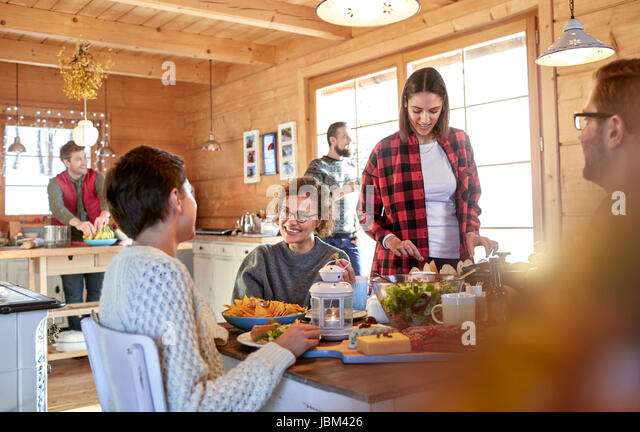Friends eating and hanging out at cabin table - Stock-Bilder