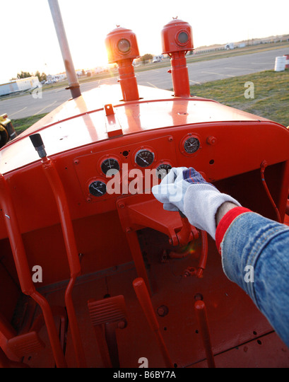 Hand operating controls in cab of earth mover - Stock Image