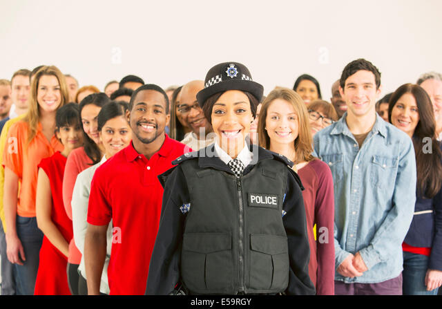 Portrait of smiling policewoman in front of large crowd - Stock Image