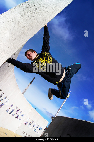 A parkour athlete performing a wall stand. - Stock Image