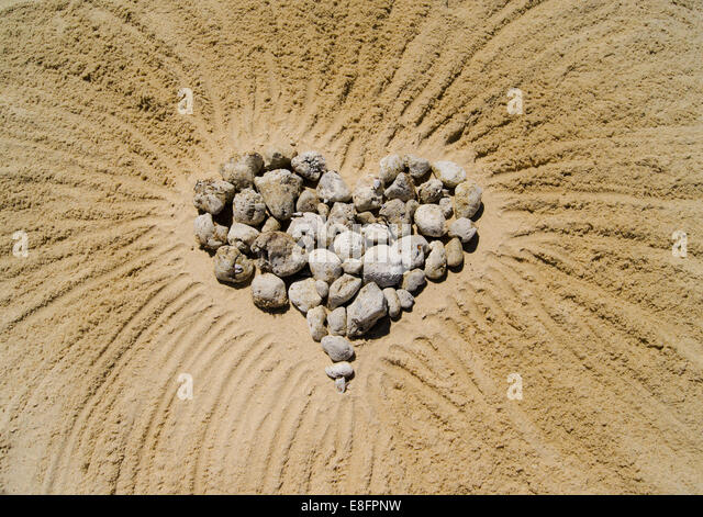 Heart made of pebbles in sand - Stock Image