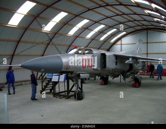 (dpa) - Visitors examine an exhibited fighter jet of the type MIG-23 of the Warsaw Pact air force in the hangar - Stock Image