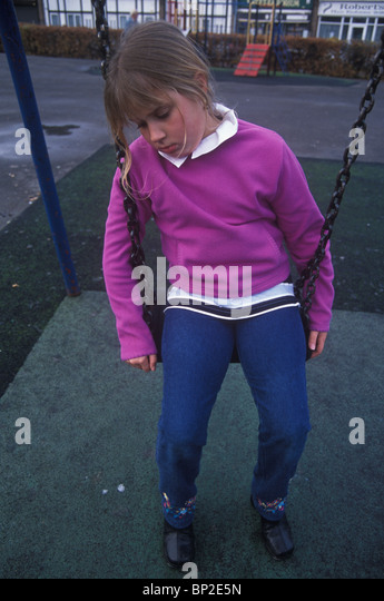 little girl on swing looking moody - Stock Image