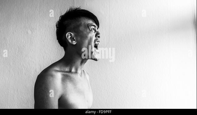 Frustrated Man Screaming At Home - Stock-Bilder