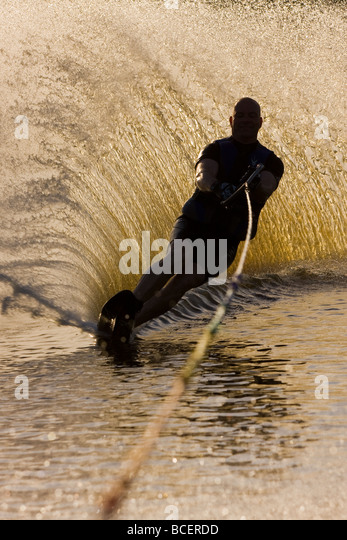 A man practicing water ski slalom in a lake in Sweden - Stock Image
