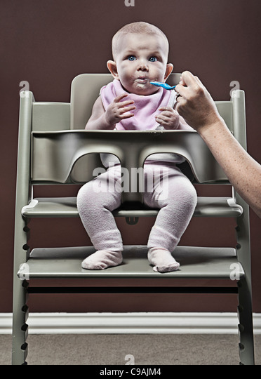 Four month old Baby Girl Eating First Food in Highchair - Stock-Bilder