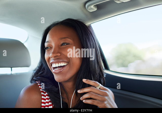 Young woman laughing car backseat - Stock Image